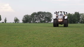Gray tractor rides on the green field Royalty Free Stock Images