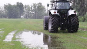Gray tractor rides on the green field Royalty Free Stock Photo