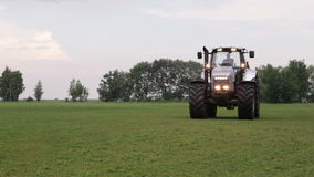 Gray tractor rides on the green field Royalty Free Stock Photography