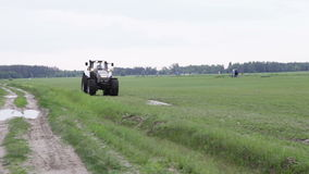 Gray tractor rides on the green field Stock Photos