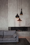 Gray velour sofa in a dark room the bright light from eternal light, and artificial fireplace. Interior loft with. Concrete walls Royalty Free Stock Photography