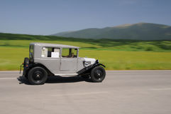 Gray vintage car  under mountains. Old timer   speeds along the under mountains landscape Stock Photos