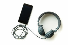 Gray vintage headphones and cellphone. Royalty Free Stock Photography
