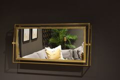 On the gray wall hangs a rectangular mirror, which reflects the room with furniture.  royalty free stock images