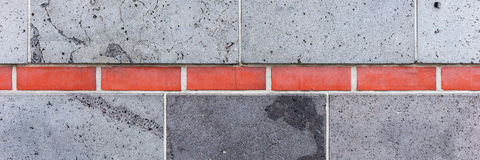 Gray wall, interrupted by red bricks. Wall background Royalty Free Stock Image