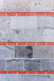 Gray wall, interrupted by red bricks. Wall background Stock Image
