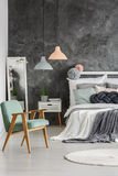 Gray wall in room. Stylish gray wall in a room with wooden bed and armchair stock image