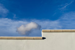 Gray wall and sky. Composition with a gray wall and blue sky and clouds Stock Photography