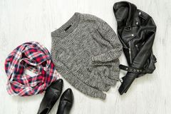 Gray warm sweater. Black jacket, checkered scarf and boots. Fash Stock Photo