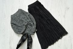 Gray warm sweater, black skirt and boots. Fashionable concept.  royalty free stock images