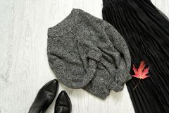 Gray warm sweater, black skirt and boots. Fashionable concept.  royalty free stock photography