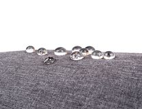 Gray waterproof fabric with waterdrops close up on white stock photography