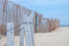 Gray and weathered storm fence slowly being covered by sand dune Stock Photography