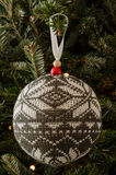 Gray and White Knitted Christmas Ornament. A gray and white knitted snowflake pattern Christmas ornament hangs on a fir tree stock photo