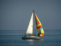Gray and White Sail Boat With 5 Person Riding on the Middle of the Body of Water Stock Photo