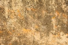 Gray white yellow old battered concrete wall with orange spots, deep scratches and stains of moss and mold. rough surface texture. A gray white yellow old royalty free stock images