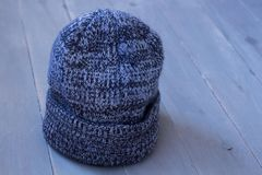 Gray winter warm hat on a wooden background. A gray winter warm hat on a wooden background Stock Images
