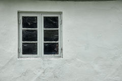 Gray wood colonial style window. One gray wood colonial style window, with spider web on the inside, fastened in a white painted plastered facade Stock Images