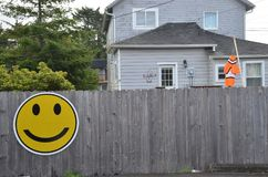 Gray Wood Fence w/ Yellow Smiley Face. This is a gray wood fence with a large yellow smiley face, and also an orange fish-shaped wind sock in Seaview, Washington royalty free stock photography