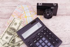 Closeup on a gray wooden table lies a camera, money calculator and a map. royalty free stock photo