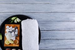 On a wooden background is a round board with towel and various pebbles for a spa procedure. On a gray wooden background with a place for an inscription there is Stock Photo