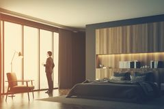 Gray and wooden bedroom, side, man. Businessman in a luxury bedroom interior with gray and wooden walls, a panoramic window, a master bed and an armchair. e view Stock Photography