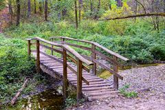 Old wooden bridge through a shallow stream in the forest. Gray wooden bridge with handrails through a shallow stream in the park stock photo