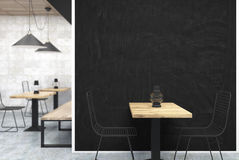 Gray and wooden cafe, black wall close up. Gray wall cafe interior with a large black wall fragment in the center, a table with a bottle near it and old oil Royalty Free Stock Images
