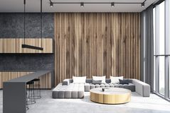 Gray and wooden living room, concrete floor. Hexagon pattern living room interior with a long gray sofa, a round coffee table standing on a concrete floor, a bar Royalty Free Stock Photos