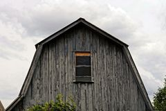 Gray wooden loft with a small window on the sky background Stock Photos