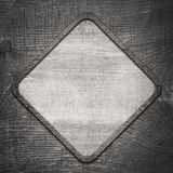 Gray wooden lozenge with frame on dark wall Stock Photos