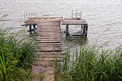 Gray wooden pier over the water near the overgrown shore Royalty Free Stock Photography