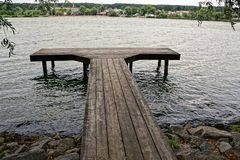 Gray wooden pier in the water near the stone shore Stock Image