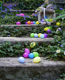 The Spilled Easter Eggs. Gray wooden stairs full of colorful easter eggs. Rattan basket on it`s side. All surrounded by blooming ground cover Stock Image