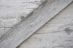 Gray wooden surface with cracks, knots and exfoliating white paint. royalty free stock photography