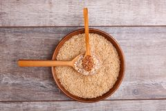 Collecting dry cereals. On a wooden background, buckwheat, rice, oatmeal in a large brown plate. On a gray wooden table in a large brown plate with rice lies a royalty free stock images