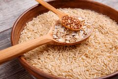 Collecting dry cereals. On a wooden background, buckwheat, rice, oatmeal in a large brown plate. On a gray wooden table in a large brown plate with rice lies a royalty free stock photo