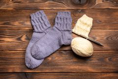 Gray woolen knitted socks and a ball of white thread with knitting needles on a wooden background royalty free stock photos