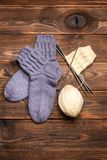 Gray woolen knitted socks and a ball of white thread with knitting needles on a wooden background stock image