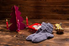 Gray woolen knitted socks, Christmas decorations and a metal box with the image of Santa Claus on a wooden background stock photos