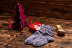 Gray woolen knitted socks, Christmas decorations and a metal box with the image of Santa Claus on a wooden background stock photography
