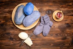Gray woolen knitted socks, knitted yarns and a cup of tea on a saucer on a wooden background royalty free stock photography