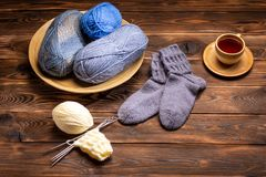Gray woolen knitted socks, knitted yarns and a cup of tea on a saucer on a wooden background royalty free stock photo