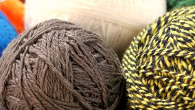 Gray, yellow-black, blue and white yarn balls stock video
