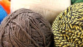 Gray, yellow-black, blue and white yarn balls stock video