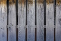 Gray yellow fence of dry wooden boards, vertical lines. rough surface texture. A gray yellow fence of dry wooden boards, vertical lines. rough surface texture stock photo