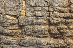 Gray yellow surface of a stone rock with deep relief and shadows. natural texture. The gray yellow surface of a stone rock with deep relief and shadows. natural royalty free stock image