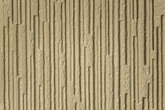 Gray yellow white beige rough surface with deep relief and shadows, vertical lines. A gray yellow white beige rough surface with deep relief and shadows royalty free stock image