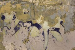 Gray yellow white heavily damaged concrete wall with peeling paint, cracks and purple spots. rough surface texture. A gray yellow white heavily damaged concrete stock photos