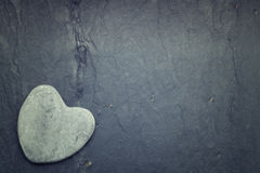 A gray zen heart shaped rock in the corner on a tile background Royalty Free Stock Images